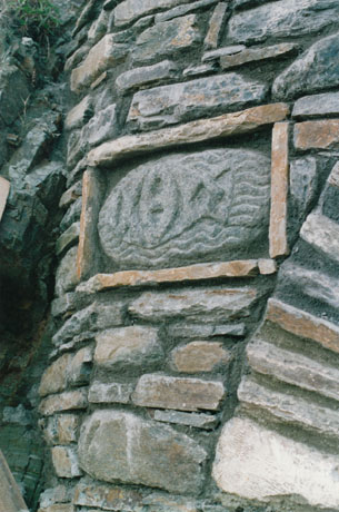ICHTHUS carving, in beach boulder set into wall